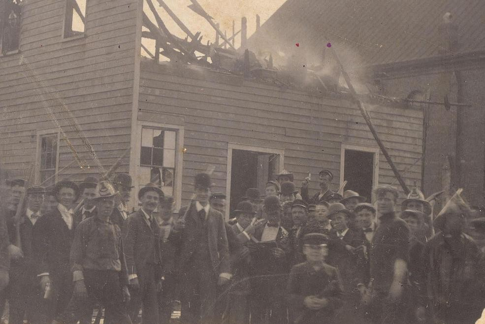 Whites pose outside torched Daily Record building on the day of the Wilmington coup.
