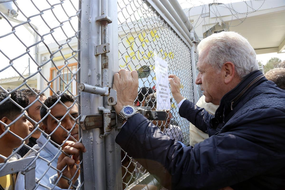 EU Migration Commissioner Dimitris Avramopoulos, right, speaks with migrants at the Moria refugee camp during his visit on the northeastern Greek island of Lesbos. Thursday, March 16, 2017.. (Manolis Lagoutaris/Pool via AP)