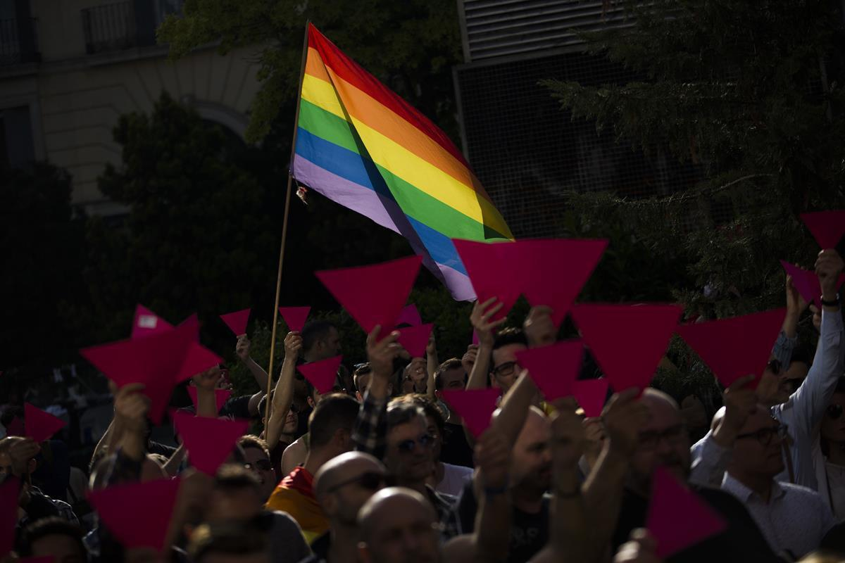 People hold up pink cardboard triangles and wave a rainbow flag during a gathering in support to the LGBT community in the Russian region of Chechnya, in Madrid, Tuesday, April 25, 2017. (AP Photo/Francisco Seco)