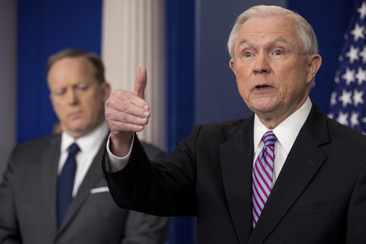 Attorney General Jeff Sessions, right, accompanied by White House press secretary Sean Spicer, talks to the media during the daily press briefing at the White House in Washington, Monday, March 27, 2017. (AP Photo/Andrew Harnik)