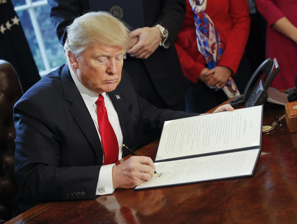 President Donald Trump signs an executive order directing the Treasury secretary to review the 2010 Dodd-Frank financial oversight law the Oval Office — Friday, Feb. 3, 2017 (AP)