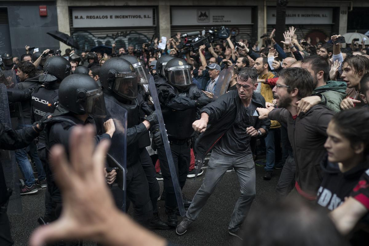 People confront Spanish riot police near a voting site at a school assigned to be a polling station by the Catalan government in Barcelona, Spain — Sunday, 1 Oct. 2017 (AP Photo/Felipe Dana, File)