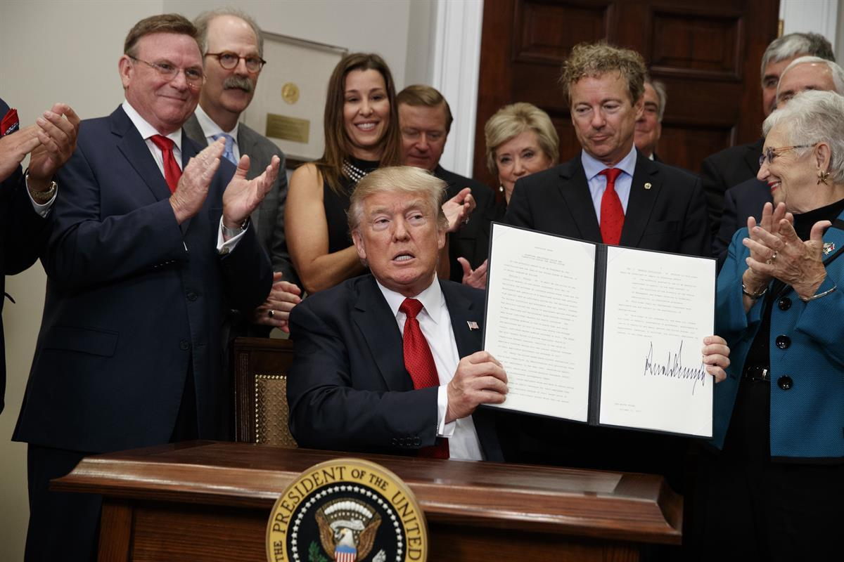 President Donald Trump shows an executive order on health care that he signed in the Roosevelt Room of the White House—Thursday, Oct. 12, 2017 (AP Photo/Evan Vucci)