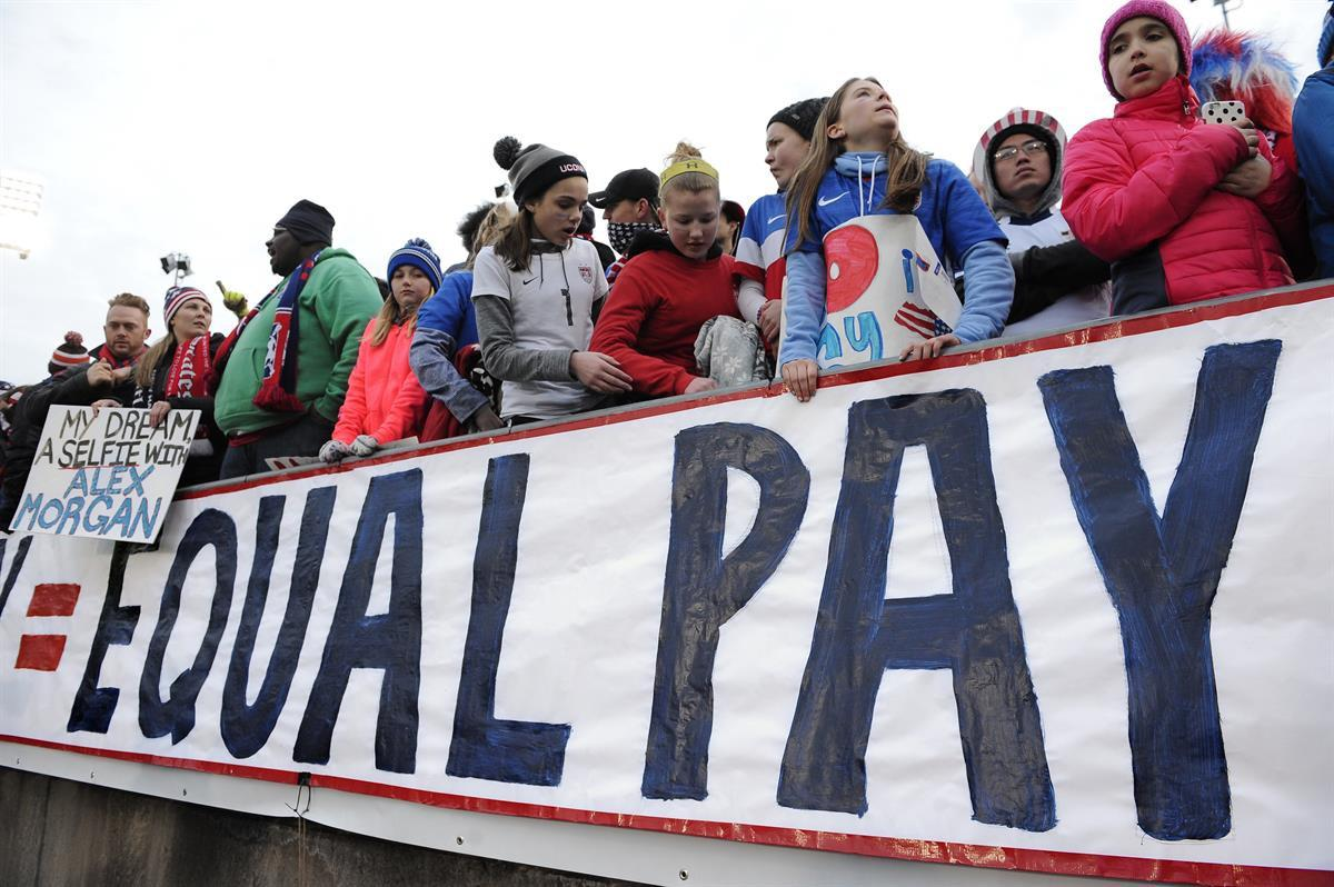 Fans stand behind a large sign for equal pay for the women's soccer team during an international friendly soccer match between the United States and Colombia at Pratt & Whitney Stadium at Rentschler Field in East Hartford, Conn. — April 6, 2016 (AP Photo/Jessica Hill, File)