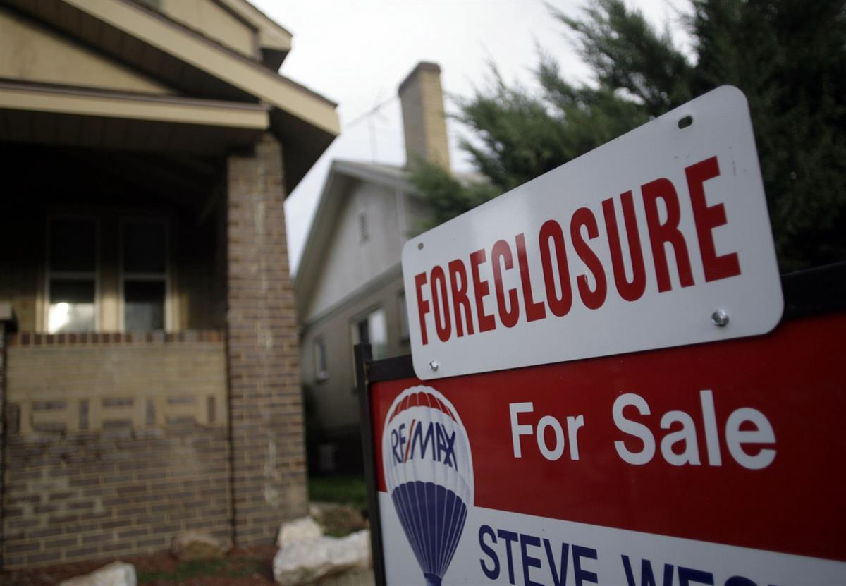 A foreclosure sign tops a sale sign outside an existing home on the market in northwest Denver — Aug. 29, 2007 (AP Photo/David Zalubowski, file)