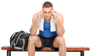Athlete sitting on bench depressed illustrating that high school athletes become heroin-addicted
