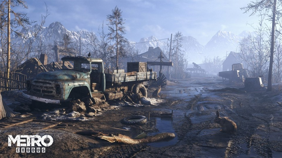 A muddy wasteland with a rabbit and rundown truck in the foreground, and snowy mountains in the background