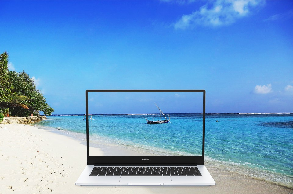 The computer showing a beachy scene with a beach in the background