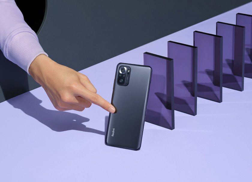 A finger taps the onyx gray Redmi phone like a domino into a series of similar purple translucent shapes, on a lilac background