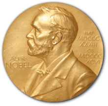 """A golden medallion with an embossed image of Alfred Nobel facing left in profile. To the left of the man is the text """"ALFR•"""" then """"NOBEL"""", and on the right, the text (smaller) """"NAT•"""" then """"MDCCCXXXIII"""" above, followed by (smaller) """"OB•"""" then """"MDCCCXCVI"""" below."""
