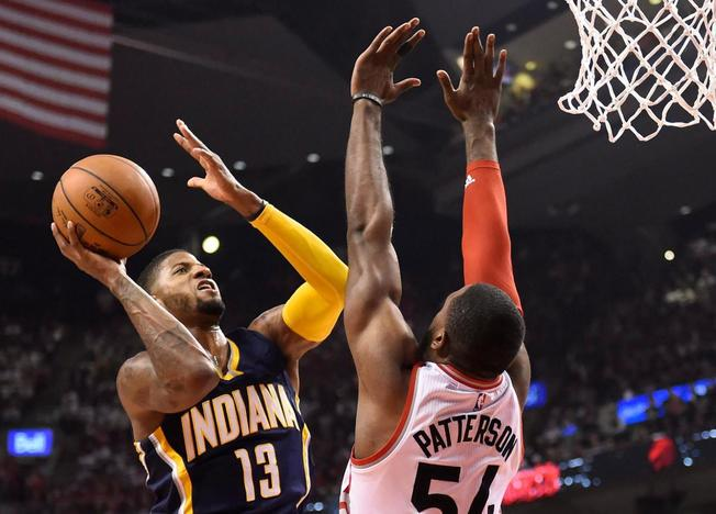 Toronto Raptors' Patrick Patterson (54) defends as Indiana Pacers' Paul George (13) drives to the net during the first half in Game 1 in the first round of the NBA basketball playoffs in Toronto, Saturday, April 16, 2016. (Frank Gunn/The Canadian Press via AP)
