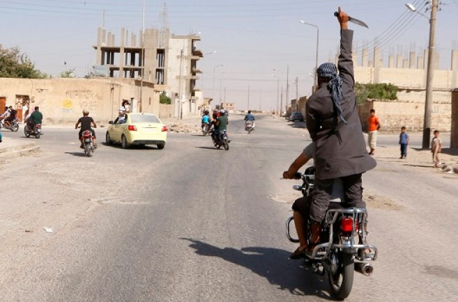 Man holds up a knife as he rides on the back of a motorcycle touring the streets of Tabqa city with others in celebration after Islamic State militants took over Tabqa air base, in nearby Raqqa city