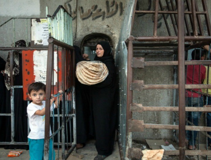 A Syrian woman carrying a bag of bread exits a bakery in Raqqa, Syria. (NB: This is not the woman to which this story refers.)