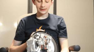 El inventor del reloj lo sostiene con la parte posterior mirando hacia la cámara para mostrarnos cómo funciona y lo mira.