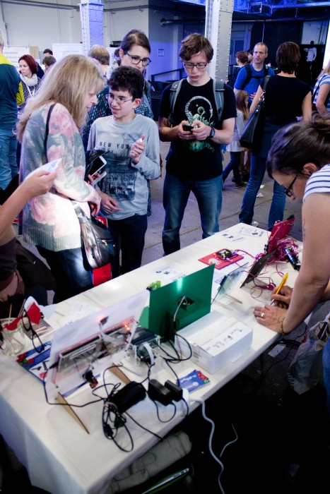 A child explains something to an adult at the Raspberry Pi booth at Maker Faire Berlin 2015