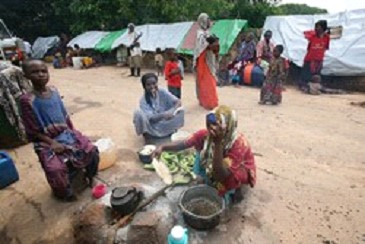 A group of Internally Displaced Somali women preparing food for their families at a makeshift camp.