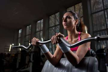 """Can You Lose Weight and Build Muscle at the Same Time?"" A woman lifts weights at the gym."