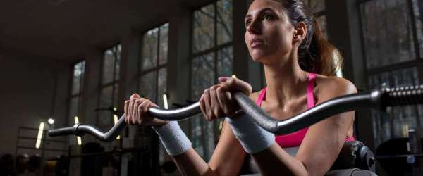 """""""Can You Lose Weight and Build Muscle at the Same Time?"""" A woman lifts weights at the gym."""