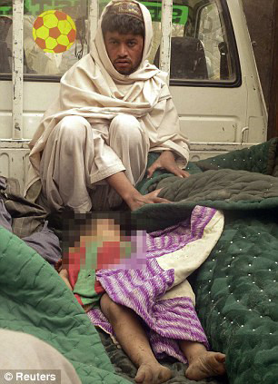A man sits in a truck bed keeping watch over the body of a young boy