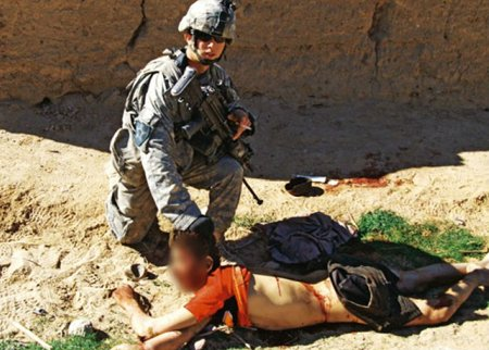 US soldier posing next to the corpse of Gul Mudin, an unarmed Afghan civilian killed by their unit on Jan. 15, 2010