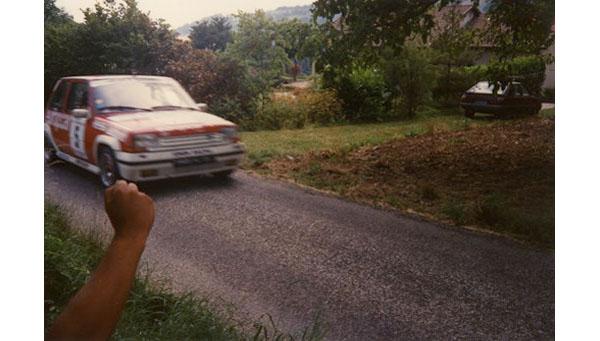 Voiture rouge et blanche arrivant sur la gauche de  l'image et voiture garée de couleur bordeaux