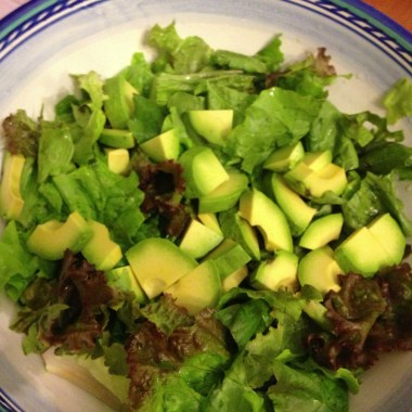 Simple Avocado Salad on a bed of red and green lead lettuce