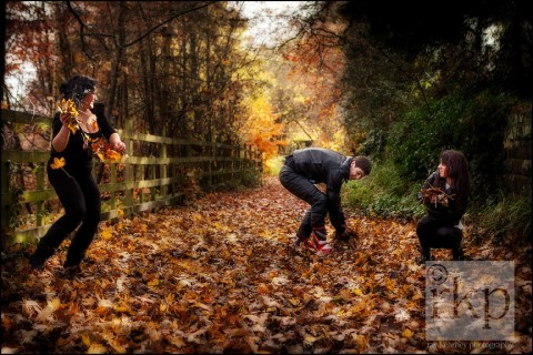 Family having a fun fight with autumn leaves in Denzell Gardens, Altrincham