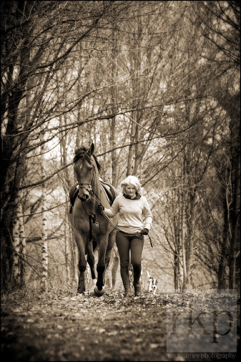 Girl walking with her horse and dog in the woods