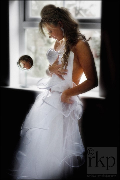Bride holding bridal dress against her