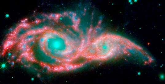 These shape-shifting galaxies have taken on the form of a giant mask. The icy blue eyes are actually the cores of two merging galaxies, called NGC 2207 and IC 2163, and the mask is their spiral arms. The false-colored image consists of infrared data from NASA's Spitzer Space Telescope (red) and visible data from NASA's Hubble Space Telescope (blue/green). NGC 2207 and IC 2163 met and began a sort of gravitational tango about 40 million years ago. The two galaxies are tugging at each other, stimulating new stars to form. Eventually, this cosmic ball will come to an end, when the galaxies meld into one. The dancing duo is located 140 million light-years away in the Canis Major constellation.The infrared data from Spitzer highlight the galaxies' dusty regions, while the visible data from Hubble indicates starlight. In the Hubble-only image (not pictured here), the dusty regions appear as dark lanes.The Hubble data correspond to light with wavelengths of .44 and .55 microns (blue and green, respectively). The Spitzer data represent light of 8 microns.