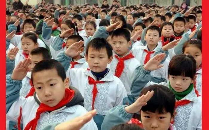 Escolares chinos en formación hacen el saludo comunista con su pañuelo rojo de pioneros comunistas