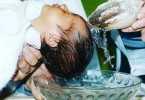 Agua bendita forma un rosario en un bautizo