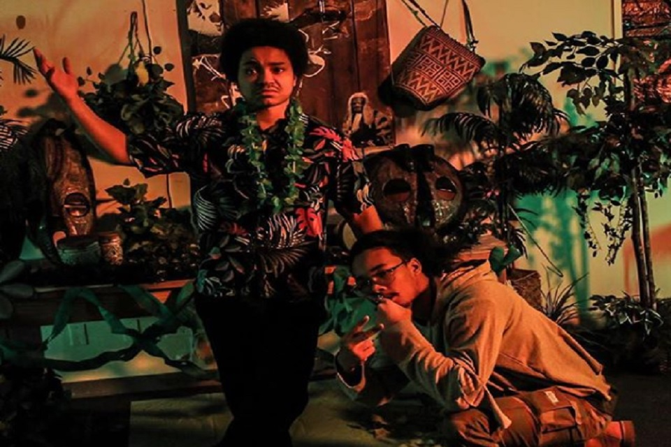 Nobi and Karma pose in tiki themed room.