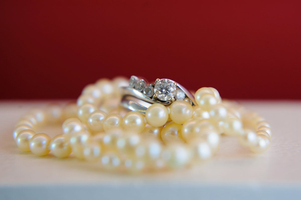 Closeup of a wedding ring set on top of a white pearl necklace