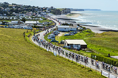 Sainte Marguerite sur Mer, France - 09 July 2015: The peloton riding near the beach in Normandy during the stage 6 of Le Tour de France 2015 on 09 July 2015.