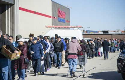 Shoppers queue up outside of Costco in North Riverside, from the front entrance to the warehouse's north end, on Friday, March 13 when panic buying began stripping grocery stores of canned goods, pasta, paper goods, water and cleaning products. | Alex Rogals/Staff Photographer