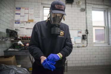 Firefighter Gianni D'Altorio pulls on gloves that are included as part of a kit every firefighter and police officer have been issued. If a serious case is suspected, paramedics may opt to use a mask fitted out with an air filter. | Alex Rogals/Staff Photographer