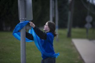 Maggie Hiestand, 12, ties a blue ribbon to a pole along the BNSF train tracks on Brookfield Avenue on April 1, in support of Maxx Kusper, who was injured by an Amtrak train in accident on March 28. | ALEX ROGALS/Staff Photographer