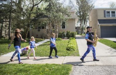 """Jim Vonesh leads his family down Herrick Road in Riverside on May 7 during one of his frequent """"sax walks"""" designed to break the stay-at-home monotony. (Alex Rogals/Staff Photographer)"""