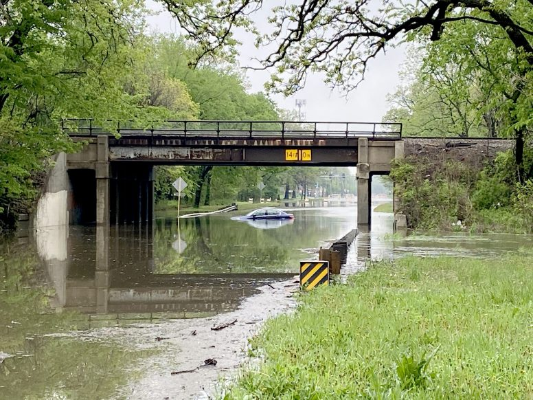 A car sits half submerged under the railroad bridge at First Avenue in Riverside on May 18 after its driver went around barricades and tried to drive through the standing water the previous evening. (Bob Uphues/Editor)