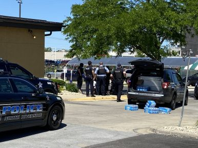 Police perform CPR on a man shot outside Olive Garden near the northeast exit to North Riverside Park Mall on Sunday, May 31. | Bob Uphues/Editor