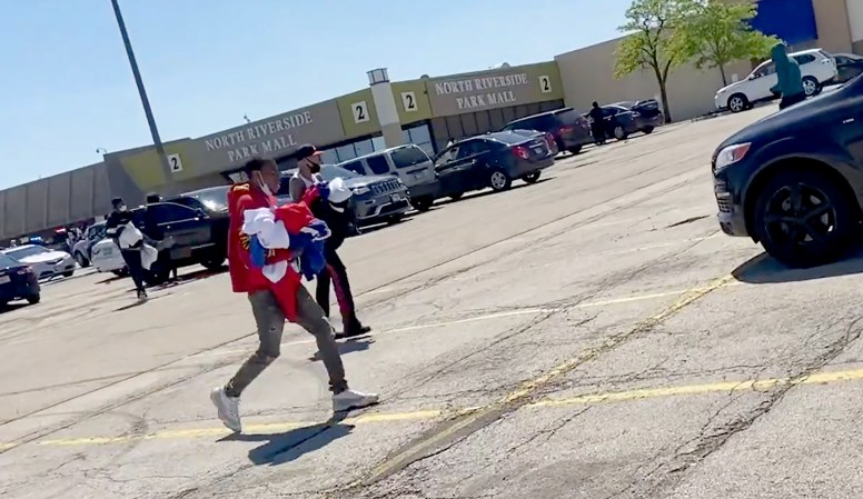 Looters carrying armloads of merchandise from the North Riverside Park Mall run back to their vehicles in the parking lot during an afternoon of violence and vandalism in the Harlem-Cermak area on May 31. (Bob Uphues/Editor)