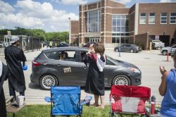 Staff and faculty cheer on the graduates lining up in vehicles on Friday, May 29, 2020, during RBHS graduation ceremony outside of the school in Riverside. | ALEX ROGALS/Staff Photographer