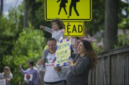 Pedestrians line up on the street and cheer on cars on Saturday, May 30, 2020, during Komarek School's graduation parade along 26th Street in North Riverside. | Alex Rogals/Staff Photographer