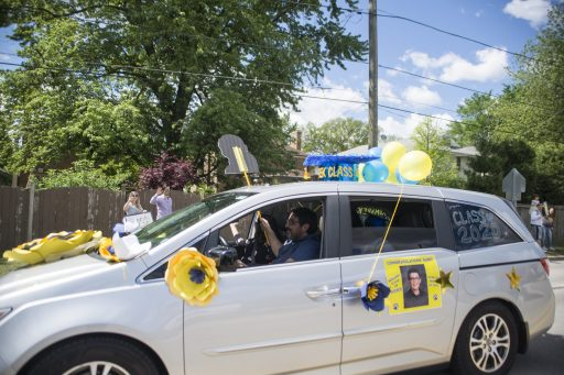 Cars carrying graduates line up down the street as people cheer on Saturday, May 30, 2020, during Komarek School's graduation parade along 26th Street in North Riverside. | Alex Rogals/Staff Photographer