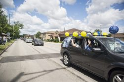 Cars drive down the road on Saturday, May 30, 2020, during Komarek School's graduation parade along 26th Street in North Riverside. | ALEX ROGALS/Staff Photographer