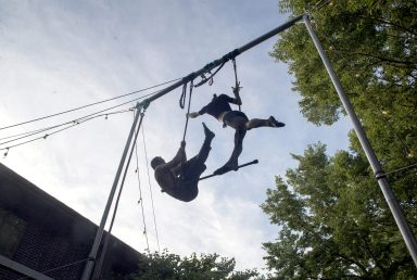 Sidelined by the pandemic, Sam Sion (left) and Sylvia Friedman sharpen their trapeze act in the backyard of their Riverside home on July 16. (Alex Rogals/Staff Photographer)