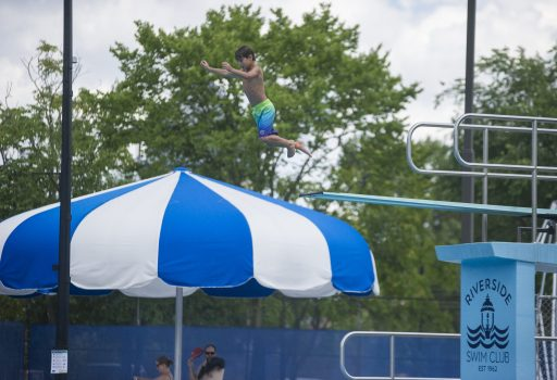 Kids jump off of the high dive on July 26, at the Riverside Swim Club in Riverside. (Alex Rogals/Staff Photographer)