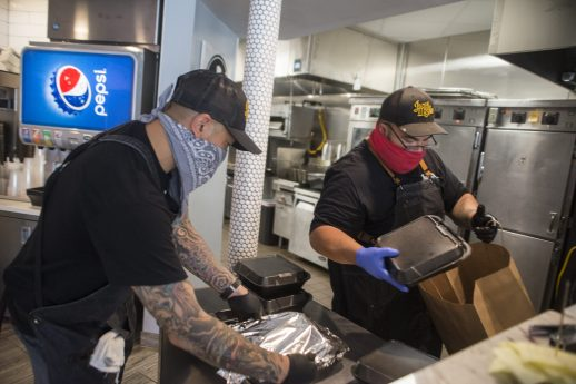 Beach Ave. BBQ owners Christopher Chin, left, and Juan Silva prepare a takeout order on Aug. 2 during brunch service at the Eight Corners eatery. (Alex Rogals/Staff Photographer)