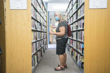 Linda Koff, of Brookfield, looks through one of the book shelves on Aug. 17, the first day the library reopened its doors to patrons for drop-in visits to browse the collection. (Alex Rogals/Staff Photographer)